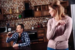Przygnębiona kobieta patrzy na pijącego męża alkoholika.
