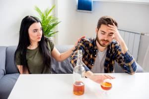 Kobieta siedzi przy stole z mężem alkoholikiem, który pije, a ona martwi się o jego stan.