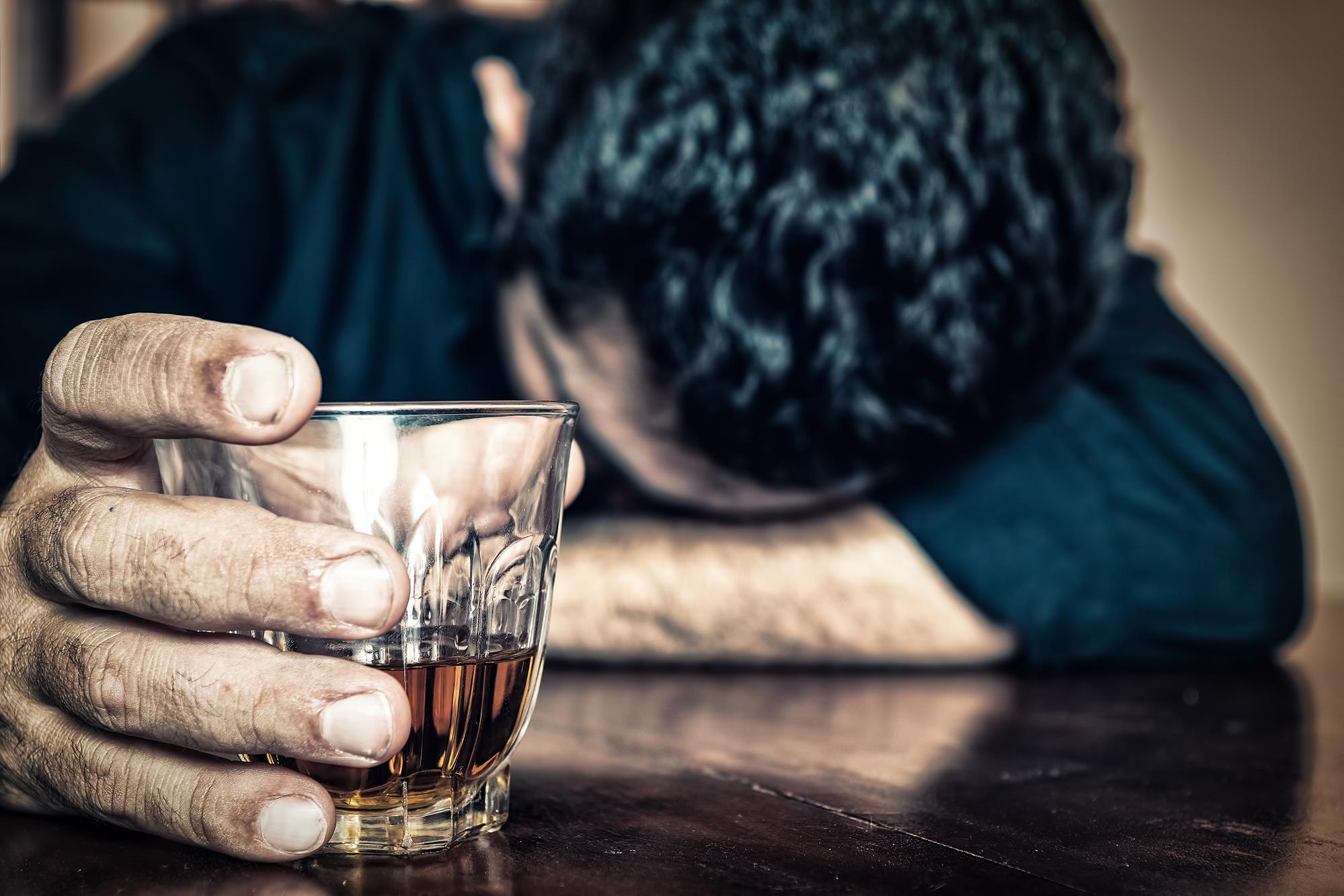 Pijany mężczyzna alkoholik leży na stole ze szklanką z alkoholem.
