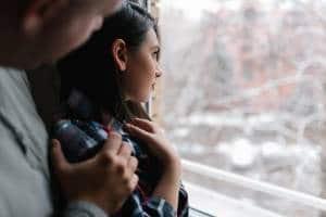 Mężczyzna uzależniony emocjonalnie trzyma za ramiona wybrankę wyglądającą za okno.