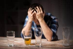 Pijany mężczyzna trzymający się za głowę